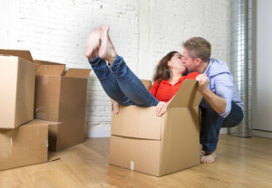 young happy American couple sitting on floor kissing celebrating moving to new house unpacking boxes in real estate concept