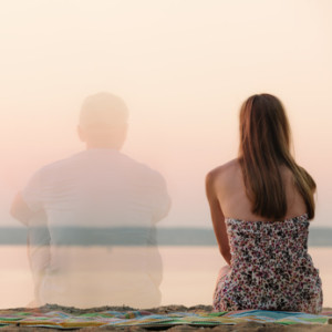Double exposure of a young couple enjoying sunset on beach
