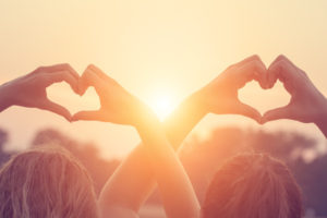 Couple of girl holding a heart-shape while watching the sunset / sunrise.